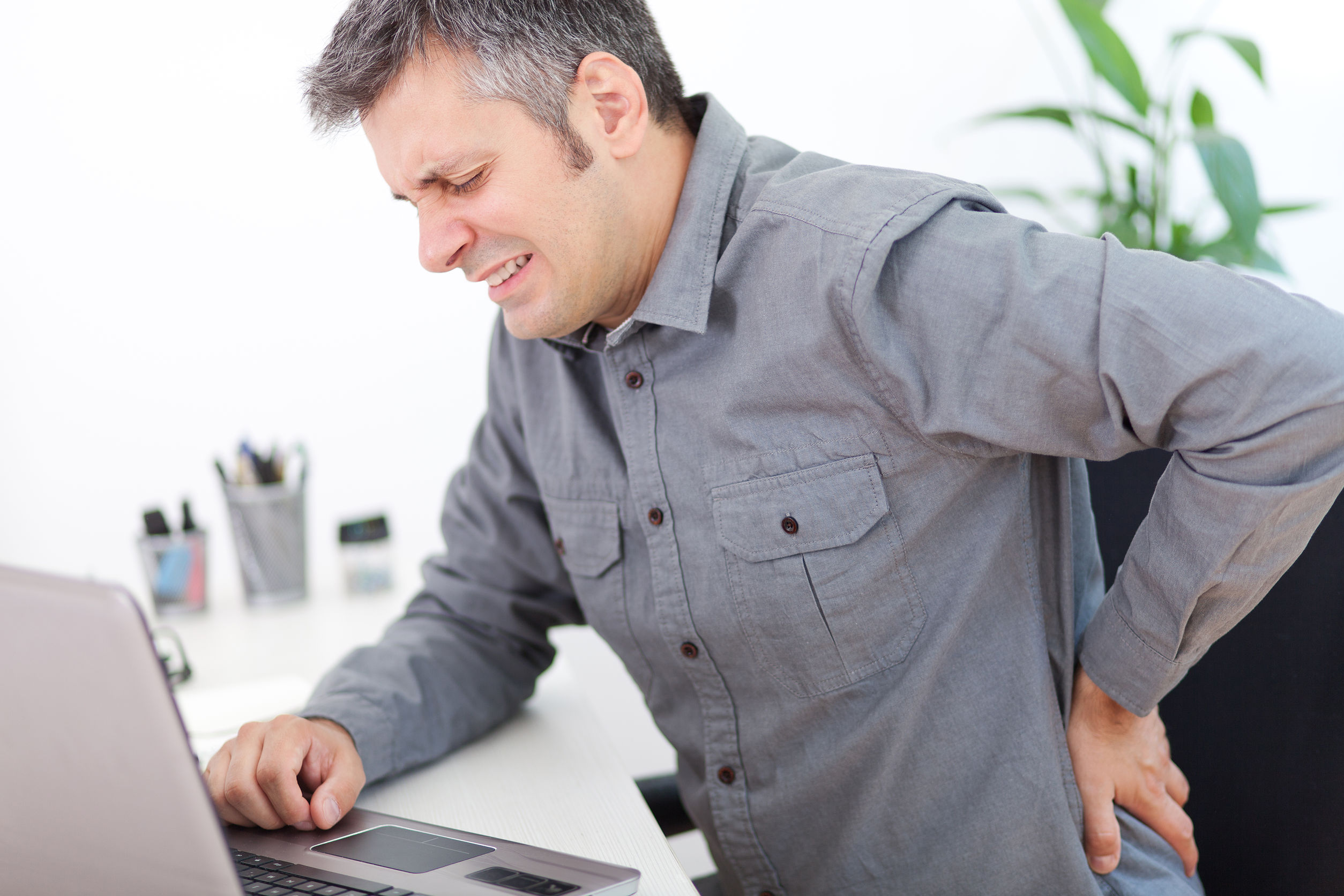 Man with back pain sitting at a desk
