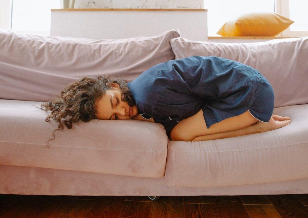 Woman lying on the sofa with chronic pain